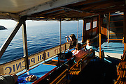 A mother, using video camera, and two children (9 years old and 5 years old) on inter-island boat, Makarska, Croatia