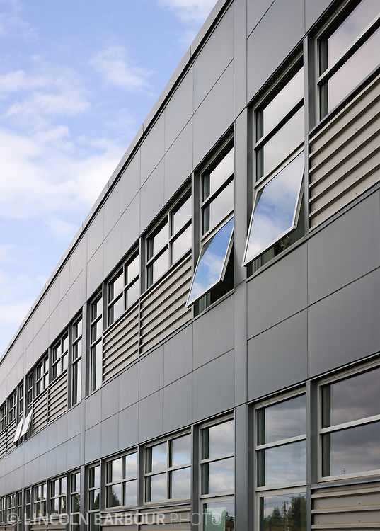 A detail view of the metal facade on a large building.  There are a few open windows and clouds being reflected in them.