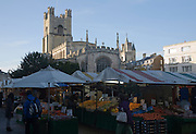 Historic tower of Great St Mary's church and market stalls in the city centre,  Cambridge, England