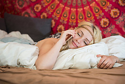 Beautiful young woman talking on smart phone in the bedroom, Bavaria, Germany