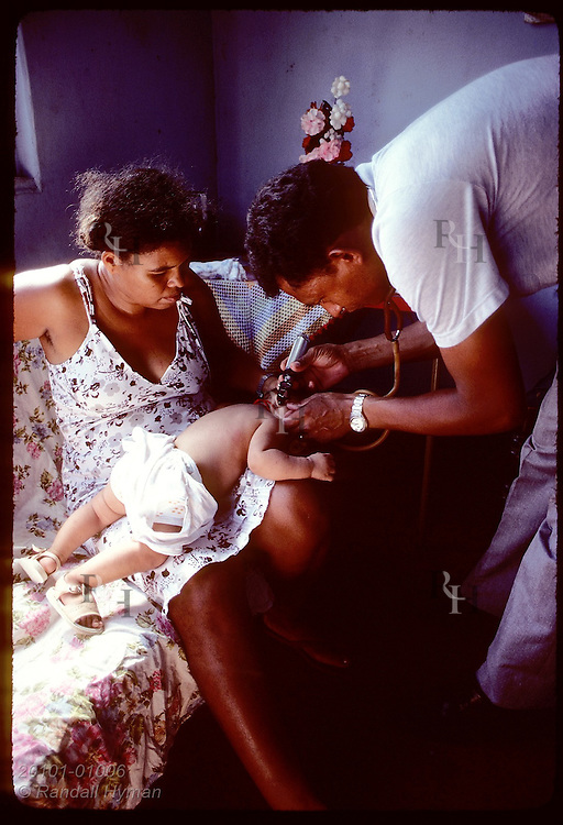 Medic from Seventh-Day Adventists' hospital ship examining sick child in the Pantanal. Brazil