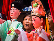 """19 FEBRUARY 2015 - BANGKOK, THAILAND:  A woman sings and manipulates puppets during a Chinese opera for Chinese opera on Yaowarat Road in Bangkok. 2015 is the Year of Goat in the Chinese zodiac. The Goat is the eighth sign in Chinese astrology and """"8"""" is considered to be a lucky number. It symbolizes wisdom, fortune and prosperity. Ethnic Chinese make up nearly 15% of the Thai population. Chinese New Year (also called Tet or Lunar New Year) is widely celebrated in Thailand, especially in urban areas that have large Chinese populations.   PHOTO BY JACK KURTZ"""