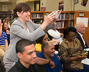 A parent photographs scholarship winners following a Broad Foundation research team tour at Ortiz Middle School, May 29, 2013.