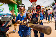 28 JUNE 2014 - DAN SAI, LOEI, THAILAND: A man carries a puppet of people having sex during the Ghost Festival parade in Dan Sai. Phi Ta Khon (also spelled Pee Ta Khon) is the Ghost Festival. Over three days, the town's residents invite protection from Phra U-pakut, the spirit that lives in the Mun River, which runs through Dan Sai. People in the town and surrounding villages wear costumes made of patchwork and ornate masks and are thought be ghosts who were awoken from the dead when Vessantra Jataka (one of the Buddhas) came out of the forest.    PHOTO BY JACK KURTZ