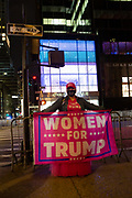 "New York, NY - 3 November 2020. New York City anticipates presidential election results as polls in some states close. A woman on Fifth Avenue near Trump Tower wears a Keep American Great hat, an All Lives Matter mask, and displays a banner that reads ""Women For Trump."""