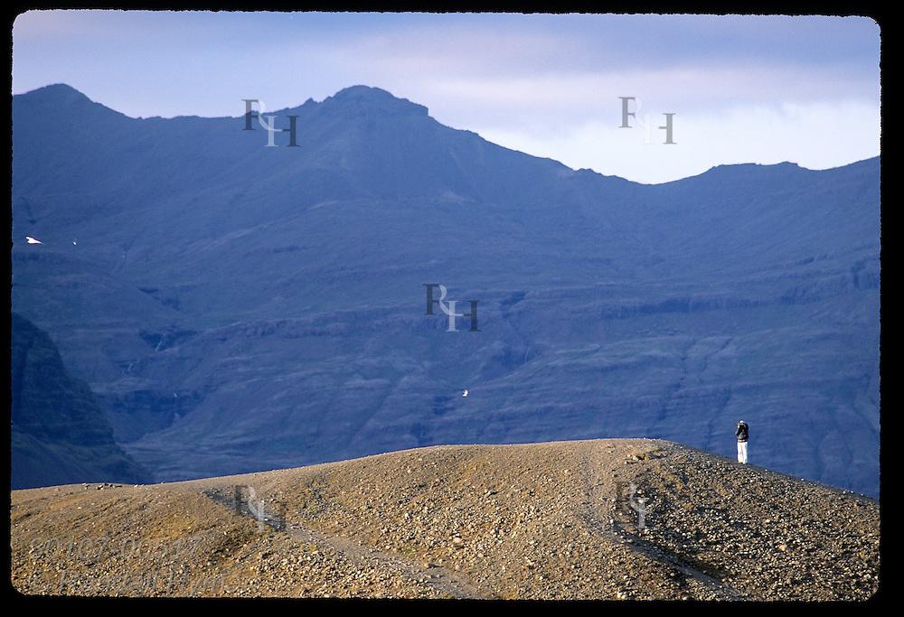 Tourist snaps photo atop rocky ridge dwarfed by mountain ridge at Breidemerkursandur; Iceland.