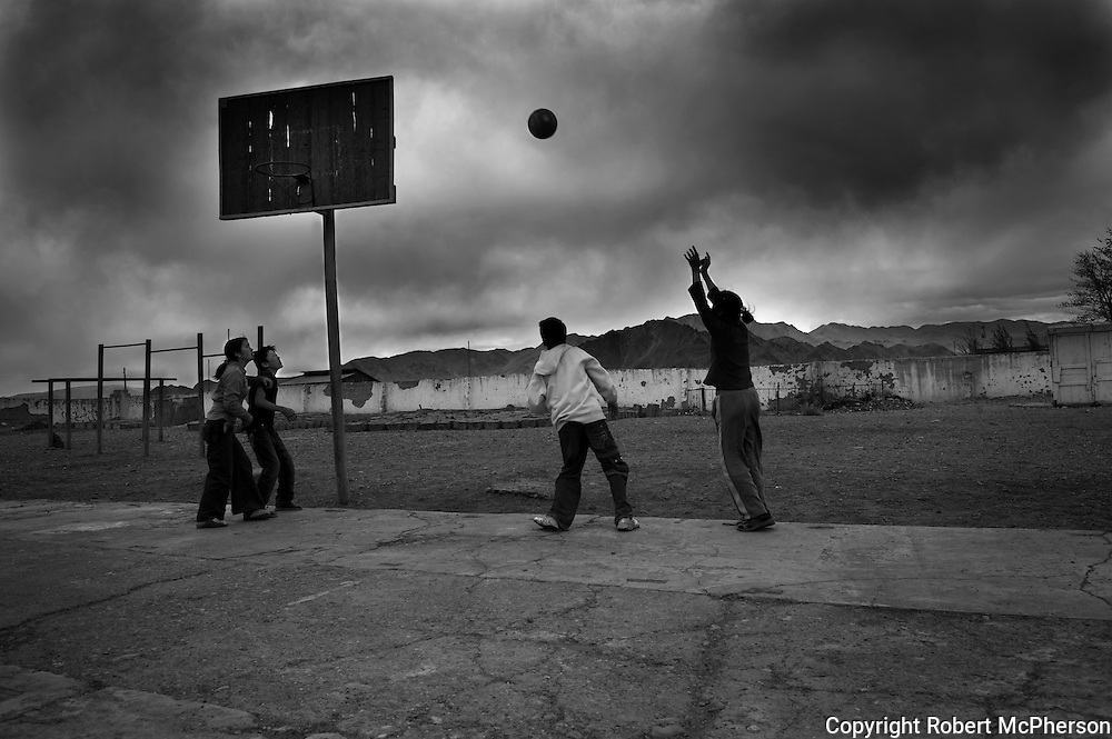 Mongolia(2008). Children playing basketball in the town of Bayan Olgii. ..Bayan Ulgii town is located in Mongolia`s western-most province. It is set in the Altai mountains where Mongolia,China and Russia converge. It is the only province where Mongolians are not the majority: about 90% of the population are ethnically Kazakh and practise Islamic traditions. Bayan Ulgii town suffered from the collapse of the socialist system; artificially created plants and industries buckled. Suddenly, all services and goods became very expensive. Today, Bayan Ulgii is the poorest province of Mongolia. Maternal and infant mortality rate is much higher than in the rest of the country and the central hospital still use Soviet made equipment waiting to be replaced.
