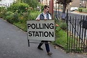 Before voting for the European Elections commences at 7am, an official carries a Polling Station sign to the entrance of St. Saviours church hall in Herne Hill, on 23rd May 2019, in Lambeth, south London, England UK.