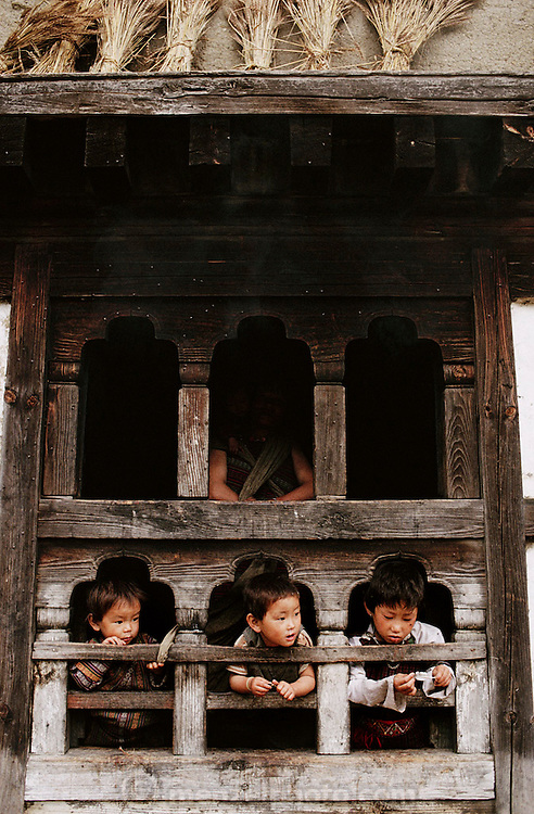 Nalim and Namgay's grandchildren look out from a hand carved window in their traditional 3-story rammed earth house. Shingkhey, Bhutan. From Peter Menzel's Material World Project.