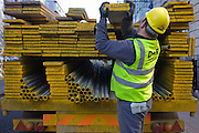 Construction site workman lifts out scaffolding boards and planks from a D+R contractor's lorry in central London.