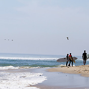 Surfers at famed Malibu Beach wait to enter the water on a warm, late summer day.