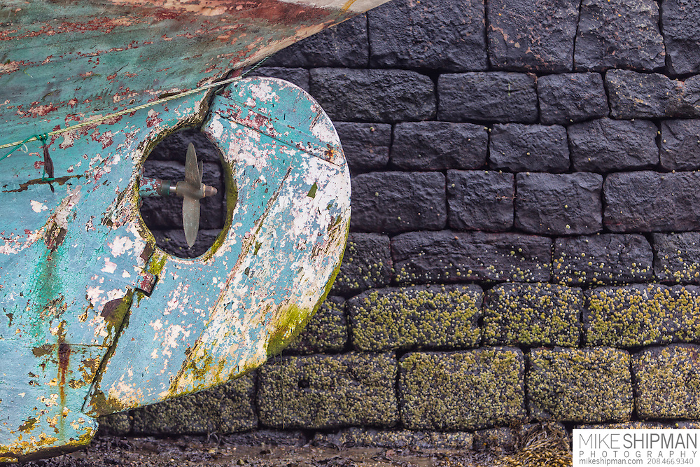 Boat rudder and propeller against stone wall, Isle of Raasay, Scotland, UK
