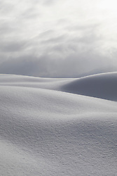 Snowcapped dunes against cloudy sky