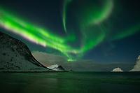Northern Lights - Aurora Borealis fill sky over snow covered mountains at Vik beach, Vestvågøy, Lofoten Islands, Norway