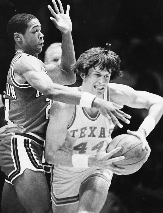 ©1985  Texas forward Mike Wacker looks to pass the ball in a college basketball dame