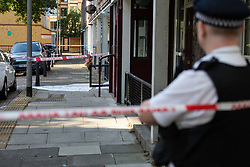 A white polythene sheet covers the spot where Paramedics were able to save the life of a 16 year-old was stabbed to death. London, August 13 2019.