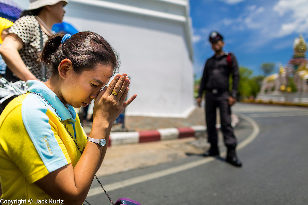 """05 MAY 2013 - BANGKOK, THAILAND:   A woman prays in the street after waiting to Bhumibol Adulyadej, the King of Thailand, Sunday. The King and Queen, who are both hospitalized and in poor health, did not attend Sunday's event. May 5 marks the 63rd anniversary of the Coronation of His Majesty King Bhumibol Adulyadej. The day is celebrated as a national holiday; since this year it falls on a Sunday, it will be observed on Monday May 6, and as such all government offices and commercial banks will close for the day. HM King Bhumibol Adulyadej is the longest reigning monarch in the world. Each year on the 5th of May, the Kingdom of Thailand commemorates the day when, in 1950, the Coronation Ceremony was held for His Majesty King Bhumibol Adulyadej, the 9th in the Chakri Dynasty (Rama IX). On the 5th of May, His Majesty conducts a merit making ceremony, presenting offerings to Buddhist monks, and leads a """"Wien Thien"""" ceremony, walking three times around sacred grounds at the Temple of the Emerald Buddha.    PHOTO BY JACK KURTZ"""