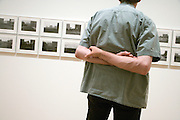 male person with his arm strangely crossed behind his back looking at a photograph exhibition Museum of Modern Art New York
