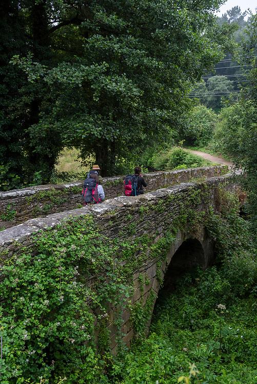 Three pilgrims walking the Camino de Santiago cross a stone bridge outside the town of Sarria, Spain. (July 7, 2018)