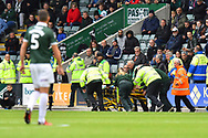 Medical staff rush a fan from the ground on a trolley after falling ill during the EFL Sky Bet League 1 match between Plymouth Argyle and AFC Wimbledon at Home Park, Plymouth, England on 6 October 2018.