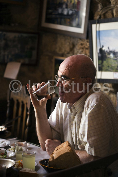 A man takes a drink from a glass whilst eating lunch at Dr. Shakshouka, a kosher Tripolitanian restaurant in Jaffa, Tel Aviv, Israel