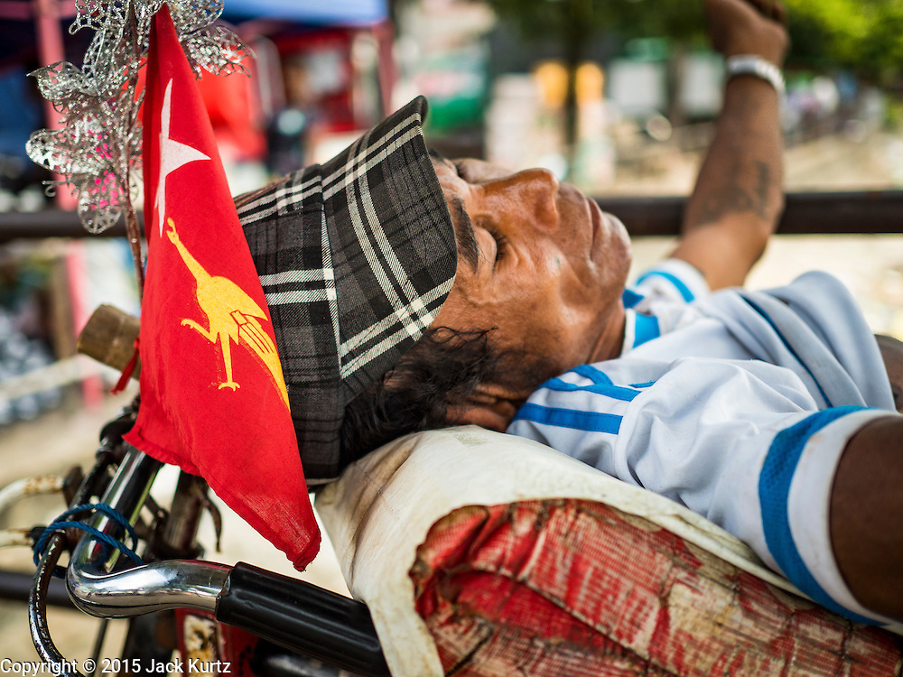 03 NOVEMBER 2015 - YANGON, MYANMAR:  A Yangon pedicab driver with a NLD flag on his pedicab takes a nap. Political parties are wrapping up their campaigns in Myanmar (Burma). National elections are scheduled for Sunday Nov. 8. The two principal parties are the National League for Democracy (NLD), the party of democracy icon and Nobel Peace Prize winner Aung San Suu Kyi, and the ruling Union Solidarity and Development Party (USDP), led by incumbent President Thein Sein. There are more than 30 parties campaigning for national and local offices.       PHOTO BY JACK KURTZ