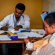 INDIVIDUAL(S) PHOTOGRAPHED: Dr. Andualem Ashine (left), Tsigereda Askale Mariam (right), and Afeam Wudu (child). LOCATION: Felege Hiwot Referral Hospital, Bahir Dar, Ethiopia. CAPTION: Dr. Andualem Ashine, a Pediatric Resident, consults Tsigereda Askale Mariam's daughter, Afeam.