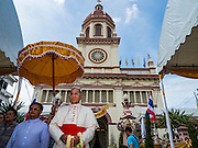18 SEPTEMBER 2016 - BANGKOK, THAILAND: FRANCIS XAVIER KRIENGSAK, (right) the Archbishop of Bangkok, greets parishioners at Santa Cruz Church before leading the church's 100th anniversary mass. Santa Cruz Church was establised in 1769 to serve Portuguese soldiers in the employ of King Taksin, who reestablished the Siamese (Thai) empire after the Burmese sacked the ancient Siamese capital of Ayutthaya. The church was one of the first Catholic churches in Bangkok and is one of the most historic Catholic churches in Thailand. The first sanctuary was a simple wood and thatch structure and burned down in the 1800s. The church is in its third sanctuary and was designed in a Renaissance / Neo-Classical style. It was consecrated in September, 1916. The church, located on the Chao Phraya River, serves as a landmark for central Bangkok.       PHOTO BY JACK KURTZ