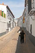 Woman walking along a quiet street in village of Jabugo, Sierra de Aracena, Huelva province, Spain