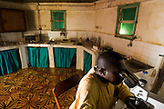 Lab technician Emile Niang analyses a stool sample in the laboratory of the traditional medicine center in Fatick, Senegal on August 6, 2009. The center mixes modern medicine techniques with African medicine provided by traditional healers.