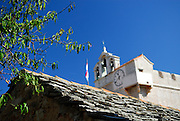 Fruit tree and traditional dry stone roof, with belltower and clock of the Church of Saint Mary in background. Village of Vrboska, island of Hvar, Croatia
