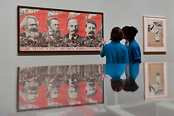 "© Licensed to London News Pictures. 07/11/2017. London, UK.  Students from Thomas Tallis School, Kidbrooke, south London, look at ""Under the Banner of Marx, Engels, Lenin and Stalin!"", 1933, by Gustav Klutsis, at a preview of ""Red Star Over Russia: A Revolution in Visual Culture 1905-55"" at Tate Modern.  The exhibition marks the centenary of the October Revolution and presents the visual history of Russia and the Soviet Union with works drawn from the late graphic designer David King. Photo credit: Stephen Chung/LNP"