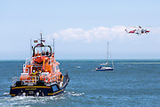 The Royal National Lifeboat Institution RNLI Dover Life boat (17-09) and HM Coastguard rescue helicopter (G-C1JW) take part in a training exercise in front of the white cliffs outside Folkestone Harbour, Folkestone, Kent. UK. 6th August 2016 (photo by Andrew Aitchison / In pictures via Getty Images)