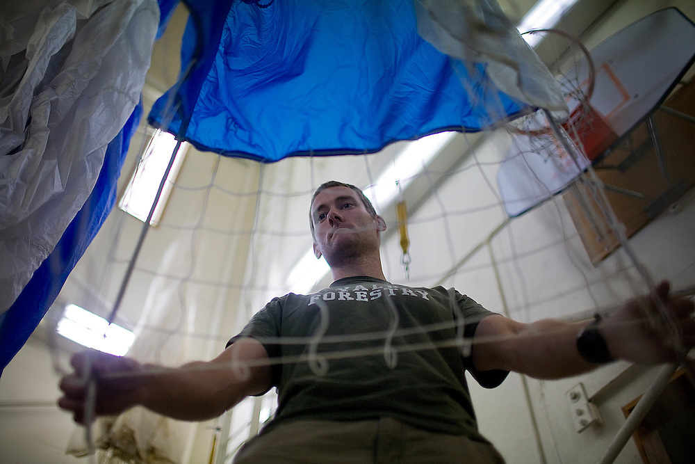 A smokejumper at McCall Smokejumper Base in McCall, ID repackages his parachute after a practice jump.
