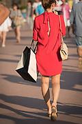 Rear view of woman in red dress walking on promenade, Cannes, France