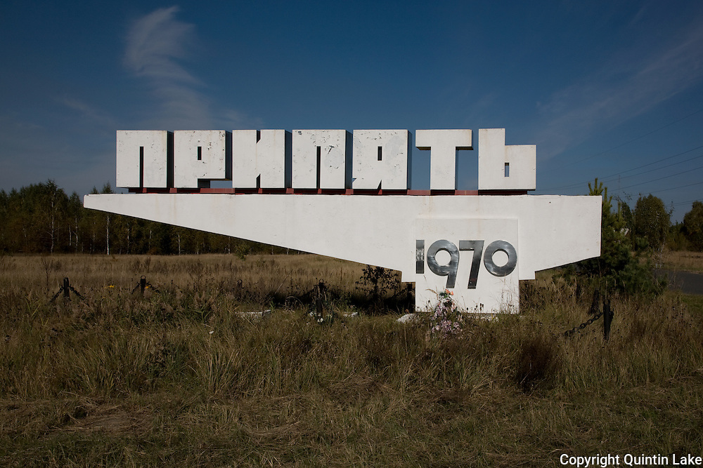 Concrete entrance sign to Pripyat. Now a memorial, it is surrounded by a steel chain  and plastic flowers.