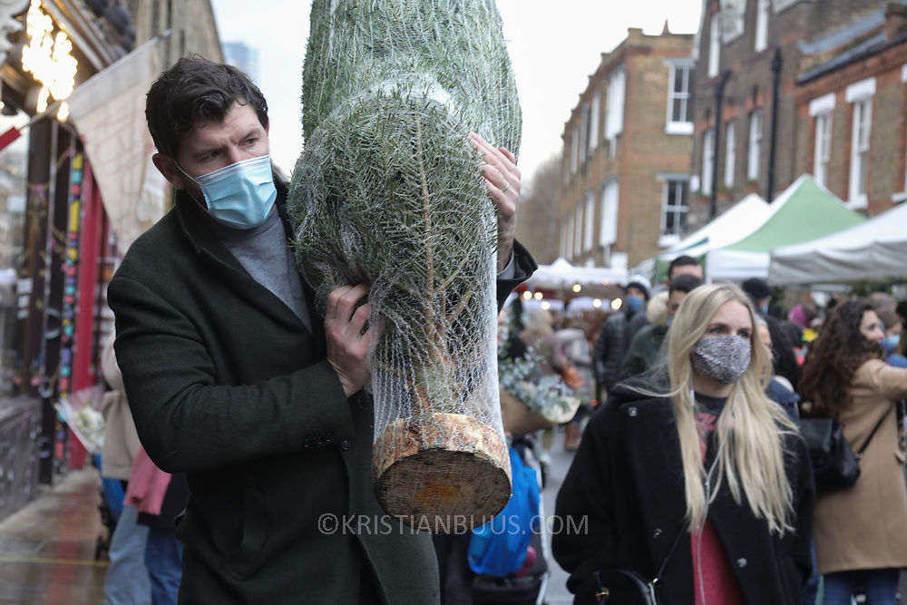 A man wearing a face mask carries a Christmas tree away in Columbia Road Flower Market, 6th of December 2020, Hackney, London, United Kingdom. The flower market in East London is all year around for all kinds of plants and flowers but at Christmas time, many come to buy their Christmas tree and decorations for the festive season. The national lockdown2 has just ended and London is under tier 2. The pandemic is still raging so many wear face masks, even outside, because of the lack of social distancing.