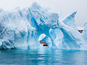 """A Zodiac boat explores a blue iceberg arch melting in Neko Harbor (an inlet of the Southern Ocean), at Graham Land, the north portion of the Antarctic Peninsula, Antarctica. Scientists have measured temperatures on the Antarctic Peninsula as warming faster than anywhere else on earth. An overwhelming consensus of world scientists agree that global warming is indeed happening and humans are contributing to it through emission of heat-trapping """"greenhouse gases,"""" primarily carbon dioxide (see www.ucsusa.org). Since the industrial revolution began, humans have increased atmospheric CO2 concentration by 35% (through burning of fossil fuels, deforesting land, and grazing livestock). Published in """"Light Travel: Photography on the Go"""" book by Tom Dempsey 2009, 2010."""