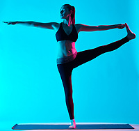 one caucasian woman exercising Hasta Padangusthasana yoga exercices  in silhouette studio isolated on blue background