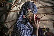 Yagana, 23, speaks to her friend on her mobile phone inside her makeshift tent in an IDP camp in Maiduguri, Nigeria, April 20, 2019. Yagana was abducted by four Boko Haram fighters in Mafa Local Government in 2014 and taken to the Sambisa Forest. When the Nigerian Military attacked their hideout in 2015, she was rescued by the army and gave birth to a baby in the military detention center in Giwa. As she was forced to leave the secondary school by BH, she wanted to continue her education and took a graduation exam on April 26, 2019.