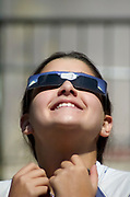 a smiling young student, looking at the sun with special glasses, during a solar eclipse on March 29th 2006 at noon
