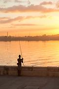 Fisherman fishing in bay at sunset under moody sky, Havana, Cuba