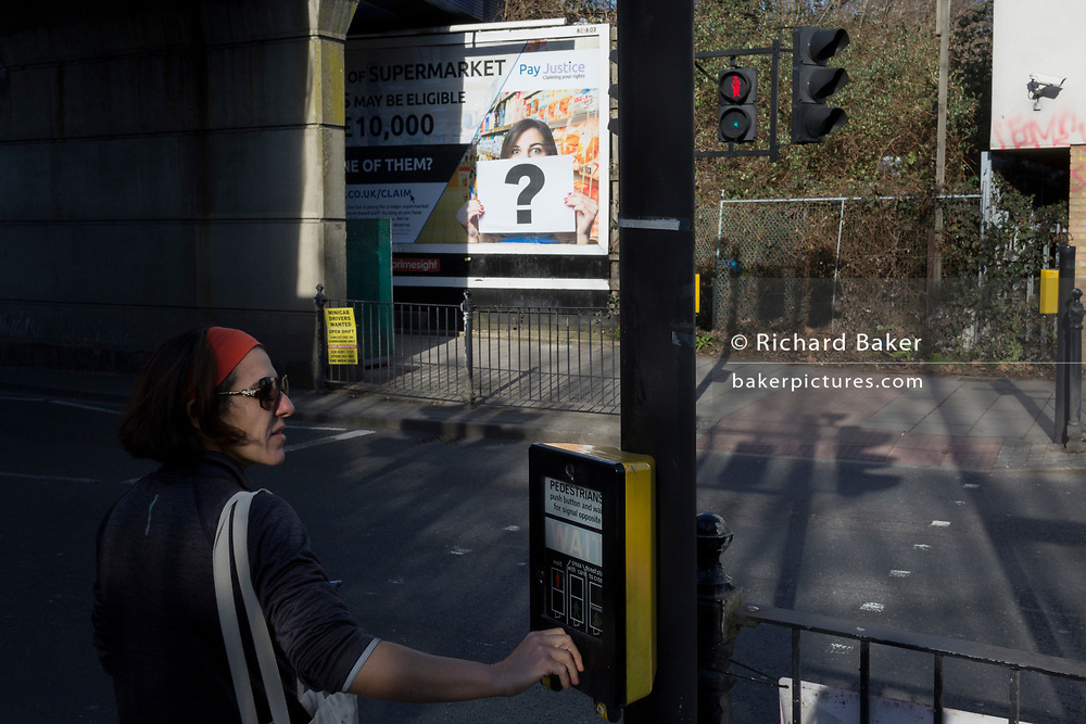 A lady presses the crossing signal in front of a question mark in the context of a billboard ad at East Dulwich, on 14th February 2019, in London, England.