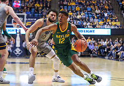 Mar 7, 2020; Morgantown, West Virginia, USA; Baylor Bears guard Jared Butler (12) drives baseline past West Virginia Mountaineers guard Jermaine Haley (10) during the first half at WVU Coliseum. Mandatory Credit: Ben Queen-USA TODAY Sports