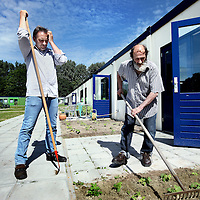 Nederland, Amsterdam , 13 juni 2014.<br /> Dakloze Arjan (l) en Max schoffelen de tuintjes voor de woningen voor dak en thuislozen van de Volksbond op het nieuwe terrein voormalig sportcomplex  op de G.J. Scheurleerweg in Amsterdam Noord<br /> Two homeless men maintain the garden of the new housing in Amsterdam, specifically for homeless people.