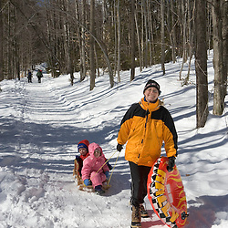 A mom and her young children on a winter adventure near the Appalachian Mountain Club's Cardigan Lodge.