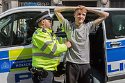 A young male protester is arrested and searched by Met police officers at Oxford Circus on day 4 of protests by climate change environmental activists with pressure group Extinction Rebellion, on18th April 2019, in London, England.