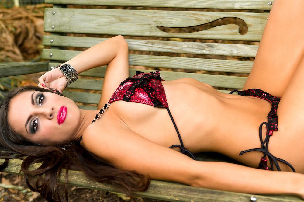 Sensual latin girl resting in a bench wearing bikini.