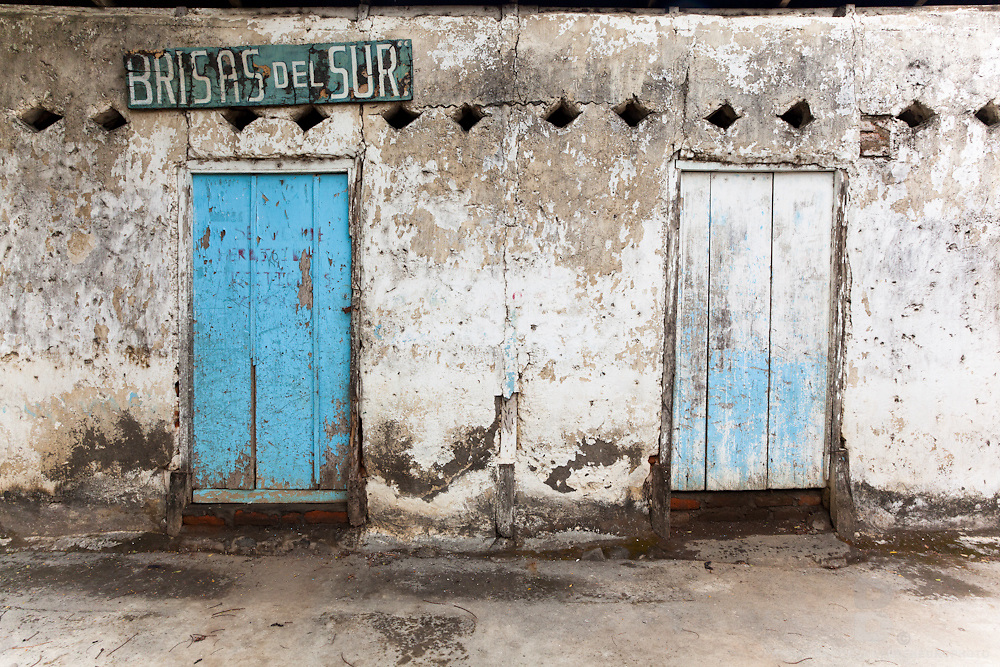 Two wooden doors of an old cement building with a old sign saying 'Brisas del Sur,' which translates to 'breezes of the south.' Captured