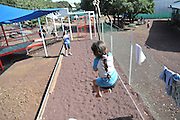 Children's holiday activity Children's adventure and playground Rear view of a girl of 5 on a zip-line